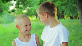 Two boys in white clothing standing in the park stock video