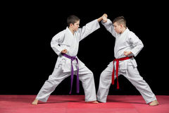 Two boys in white kimono fighting isolated on black background stock image