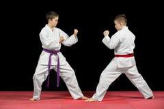 Two boys in white kimono fighting isolated on black background Stock Photo