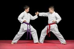 Two boys in white kimono fighting isolated on black background Stock Photos