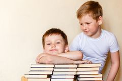 Two boys in white t-shirts at the table with books. Indoors royalty free stock image