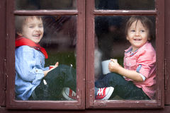 Two boys on the window, laughing and drinking tea Royalty Free Stock Image