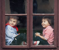 Two boys on the window, laughing and drinking tea Royalty Free Stock Photos