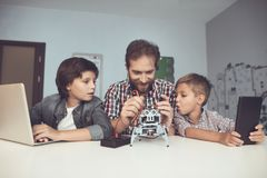 Two boys work on a tablet and a laptop, between them a man sits and constructs a robot. Two boys work on a tablet and a laptop, between them a men sits and Royalty Free Stock Photo