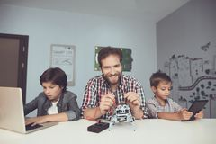 Two boys work on a tablet and a laptop, between them a man sits and constructs a robot. Two boys work on a tablet and a laptop, between them a men sits and Royalty Free Stock Images