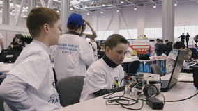 Two boys working on a computer science fair. Two boys working at the computer in the science fair. On the table, a small robot with wheels. 4K video stock video