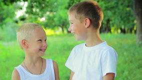 Two boys 8 years and 5 years in a white dress. Standing in the park looking at each other laughing and  pretending faces stock video