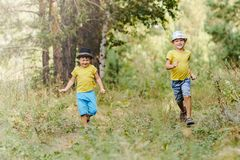 Two boys in in the yellow shirts and hats running through the woods stock photos