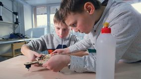Two boys young engineers making drone model. 4K. Two boys young engineers making drone model stock footage