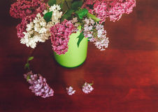 Two Branch of White and Purple Lilac in the Green Plastic Pitcher.Wooden Table Stock Photo