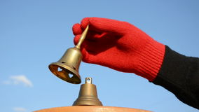 Two brass bells and hand with glove. Two brass bells and hand with red glove stock footage
