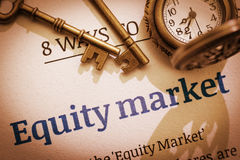 Two brass keys and a pocket watch on an equity market principal / fundamental document. Stock Images