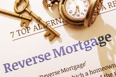 Two brass keys and a pocket watch on a reverse mortgage instruction document. Stock Photography