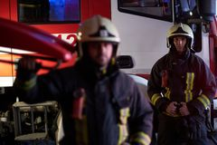 Two brave firemen wearing a protective uniform standing next to a fire truck. Arrival on call at night time stock image