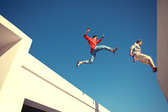 Two brave men jumping over the roof. And little motion blur royalty free stock photo