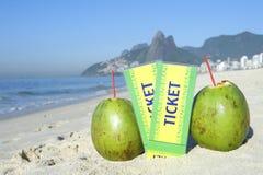 Two Brazil Tickets with Coconuts Ipanema Beach Rio. Two Brazil tickets in the sand with coconuts on the Ipanema Beach in Rio de Janeiro with Dois Irmaos Mountain Stock Photos