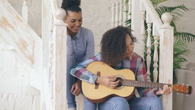 Two brazilian curly girls sistres sitting on stairs and practice to play acoustic guitar. Friends have fun and singing.  stock footage