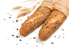 Two bread with mix seed grain cereals. Two baguettes baked bread in paper with different seeds pumpkin, poppy, flax, sunflower, sesame, millet decorated with royalty free stock photo