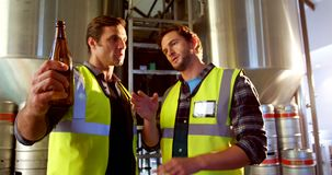 Two brewers checking beer bottles 4k. Two brewers checking beer bottles in brewery factory 4k stock footage