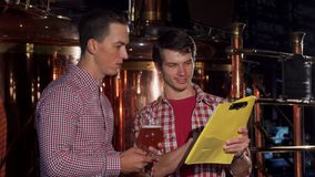 Two brewers examining craft beer, working at the brewery stock images