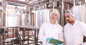 Two brewery workers working together. In the factory stock footage