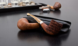Two briar and case. Two briar pipe on sofa with case Royalty Free Stock Photography