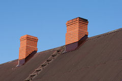 Two brick chimney. Bricks chimney on the dark metal-sheet roof stock image