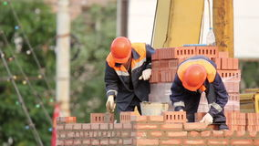 Two bricklayer building a brick wall. The masons wearing helmets and overalls on June 17, 2016 in Novokuibishevsk/Samara region/Russia stock video