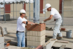 Two Bricklayers. One is adding mortar while the other is leveling brick row in column Royalty Free Stock Image