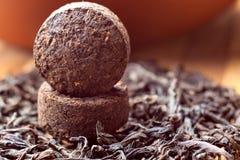 Two bricks of old aroma tea pu-erh. On dry tea background Stock Photo