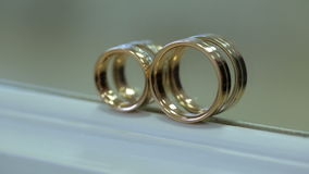 Two bridal golden rings stand on white windowsill. They are prepared for wedding ceremony for newlyweds, which they put on fingers of each other in sign of stock footage
