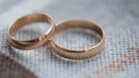Two bridal rings lie on knitted surface of tablecloth. They are made from gold and shine brightly under light of noontime sun which penetrates through window stock video
