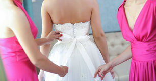Two bride-maids in fuchsia dresses bustling the wedding dress. Bride-maids hands ribbon making on the back of bride white dress Stock Photos