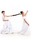 Two Brides Fighting. Two young beautiful brides in white dresses on white isolated background. One of them is pulling others ponytail and smiling Royalty Free Stock Images