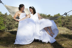 Two brides in hammock against blue sky with forest background Royalty Free Stock Photo