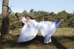 Two brides in hammock against blue sky with forest background Stock Photo