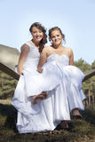 Two brides in hammock against blue sky with forest background Stock Photography