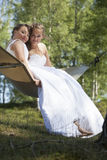 Two brides in hammock against blue sky with forest background Royalty Free Stock Photos