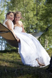 Two brides pose on hammock in forest on sunny summer day Royalty Free Stock Photography