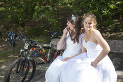 Two brides pose on wooden bench in forest with mountain bikes ne Stock Images