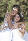 Two brides smile and embrace in nature surroundings Royalty Free Stock Images