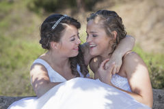 Two brides smile and embrace in nature surroundings Stock Photography