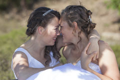 Two brides smile and embrace in nature surroundings Royalty Free Stock Photos