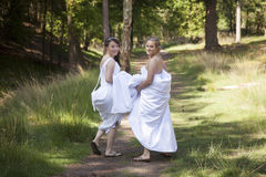 Two brides walk on forest path with skirts in their arms Stock Images