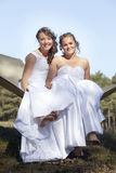Two brides in white dresses pose on hammock in forest on sunny s Stock Photo