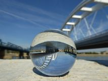 Two bridges on the river Danube reflection in crystal ball. With blue sky background royalty free stock photos