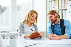 Two at briefing. Woman assigning tasks for man stock image