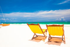 Two briggt yellow chairs on caribbean beach of Stock Images