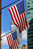 Two bright american flags and the skyscrapers in a sunny weathe Royalty Free Stock Photos