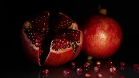 Two bright big grenades on a black background. Two bright big juicy pomegranates on a black background stock video footage